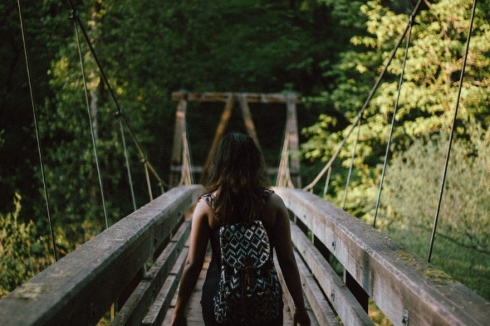 woman-walking-on-bridge-in-forest