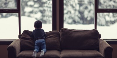 young child looking out window to snow scene